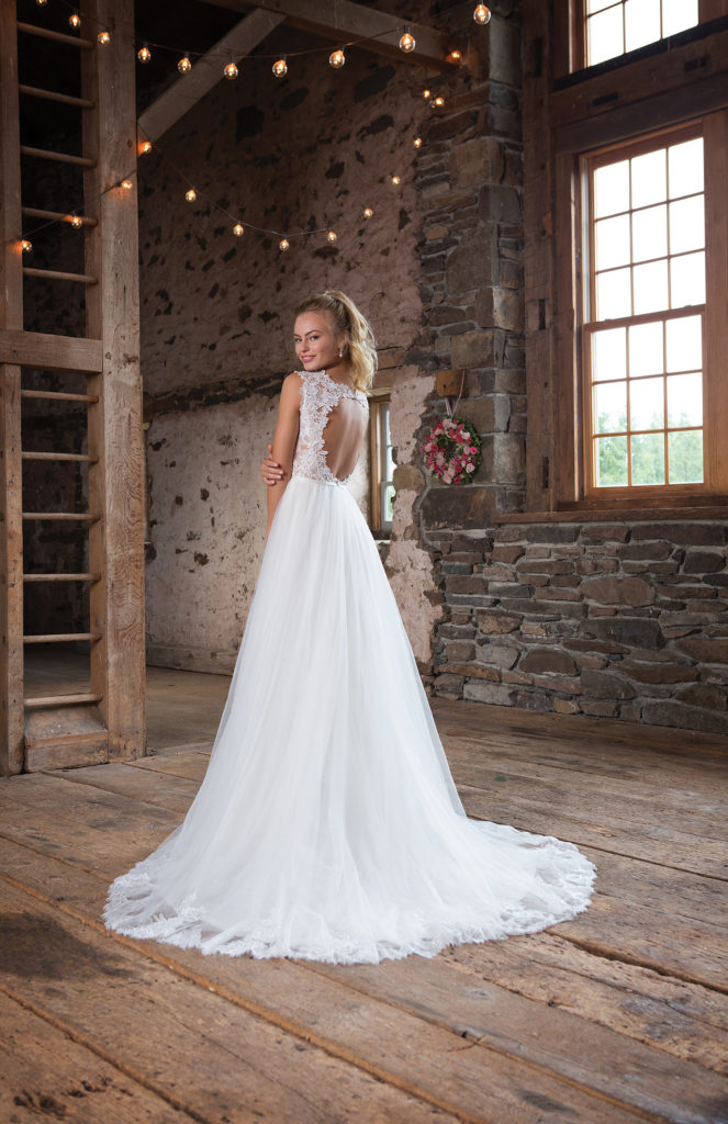 Sweetheart Gown 1100 - Fun and flirty details create this gown with a deep V illusion neckline, keyhole back, and attached belt at the natural waistline. A simple tulle skirt with finished hem lace completes the look - The Blushing Bride boutique in Frisco, Texas