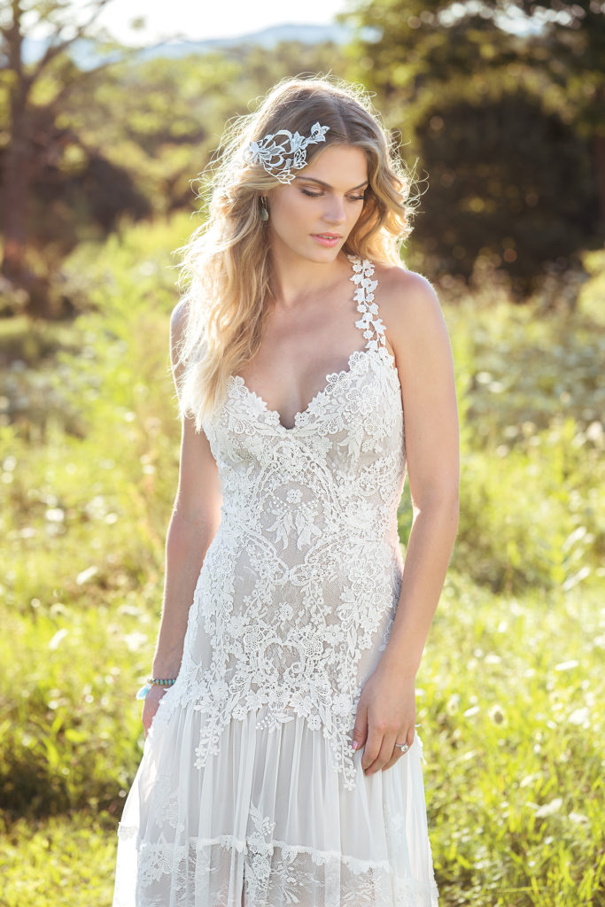 Lillian West 6491 - Drape yourself in boho glamour with this gypsy-inspired gown. Beautiful Chantilly and Venice lace cover the bodice and a tiered skirt made of lace and chiffon feels like it's from another era - The Blushing Bride boutique in Frisco, Texas